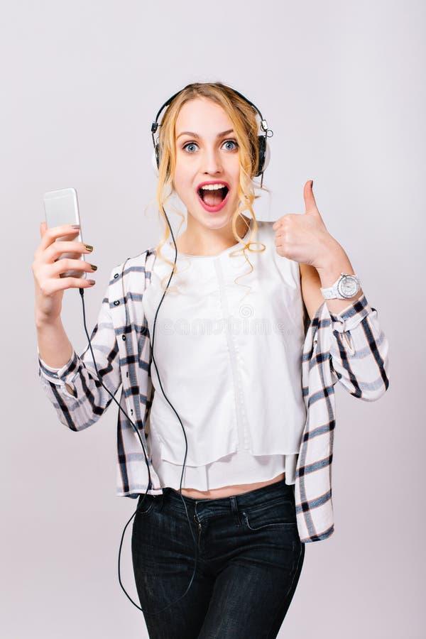 Giovane ragazza allegra graziosa con il iPhone a disposizione Bionda splendida allegra negli alti alcoolici che ascolta la musica immagine stock libera da diritti
