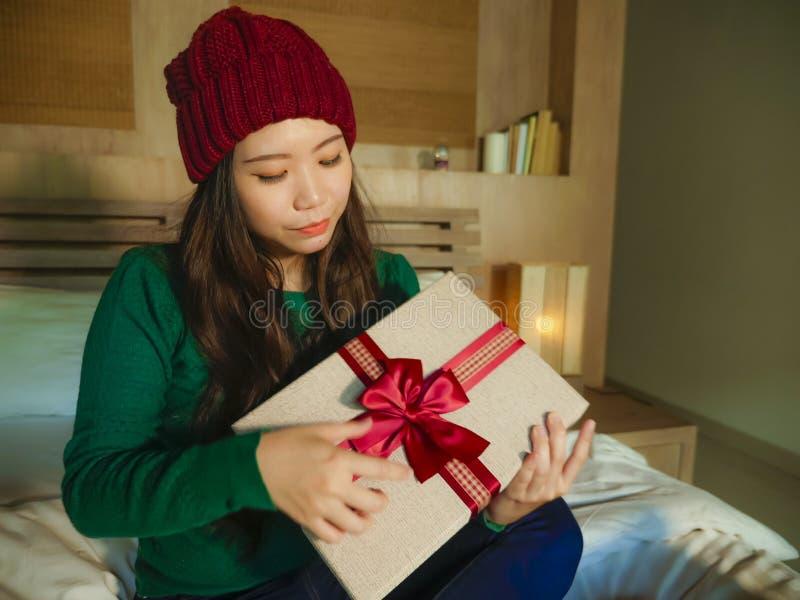 Giovane ragazza americana asiatica felice e bella in cappello di inverno che giudica la scatola del regalo di Natale con sorrider immagine stock