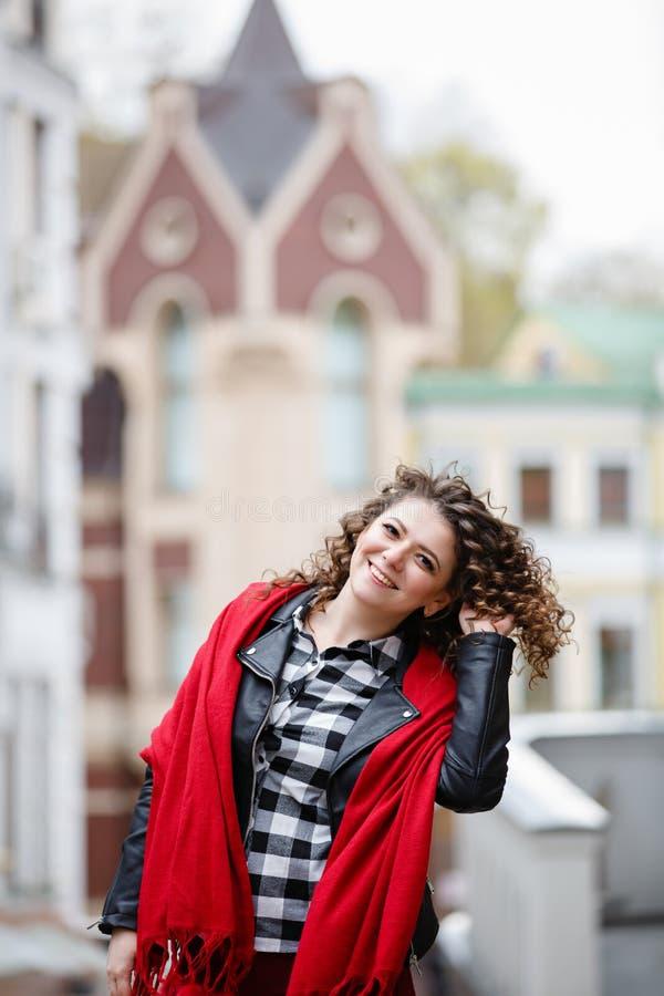 Giovane ragazza arricciata weared in bomber nero e sciarpa rossa su fondo di vecchia citt? fotografia stock