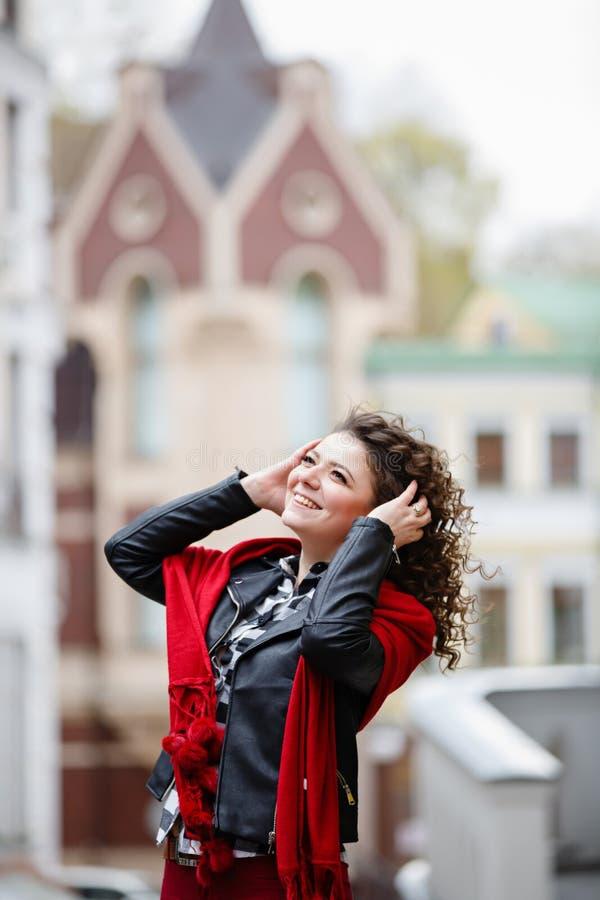 Giovane ragazza arricciata weared in bomber nero e sciarpa rossa su fondo di vecchia citt? immagini stock