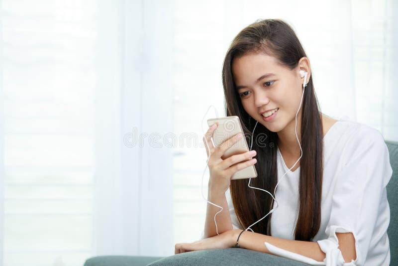 Giovane ragazza asiatica che ascolta la musica con la cuffia e lo smarthpho immagine stock
