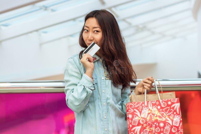 Giovane ragazza asiatica che fa spesa in un centro commerciale immagini stock libere da diritti