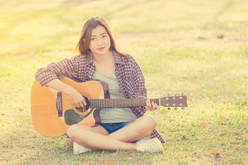 Giovane ragazza asiatica che gioca chitarra fotografia stock libera da diritti