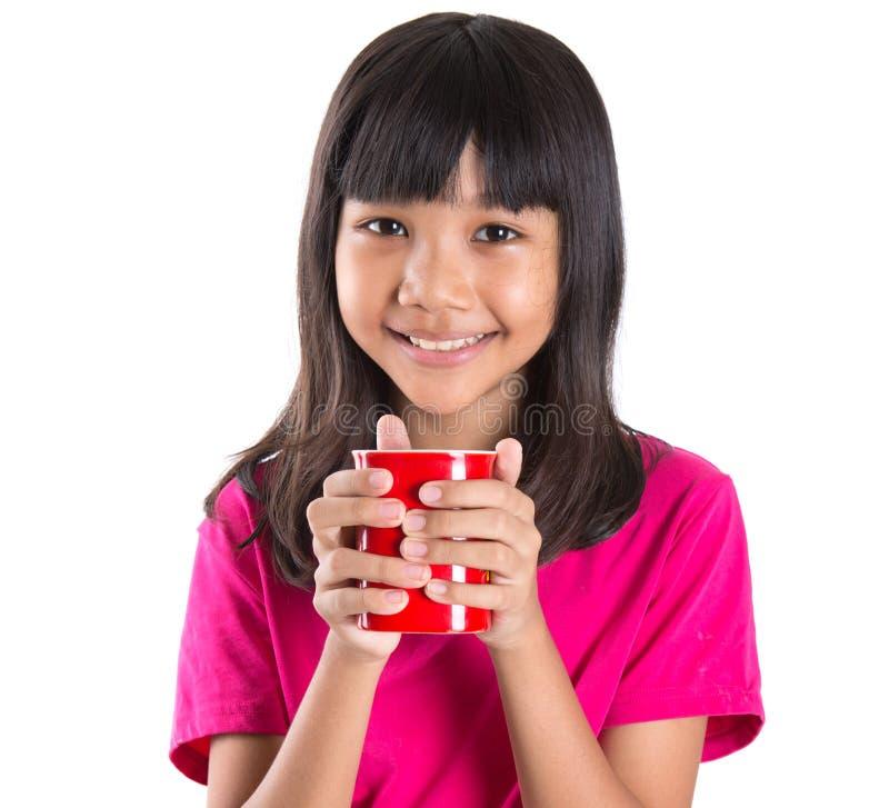 Giovane ragazza asiatica con la tazza rossa VII fotografia stock libera da diritti
