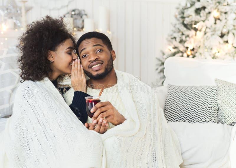 Giovane ragazza attraente che bisbiglia al suo uomo sorridente fotografie stock libere da diritti