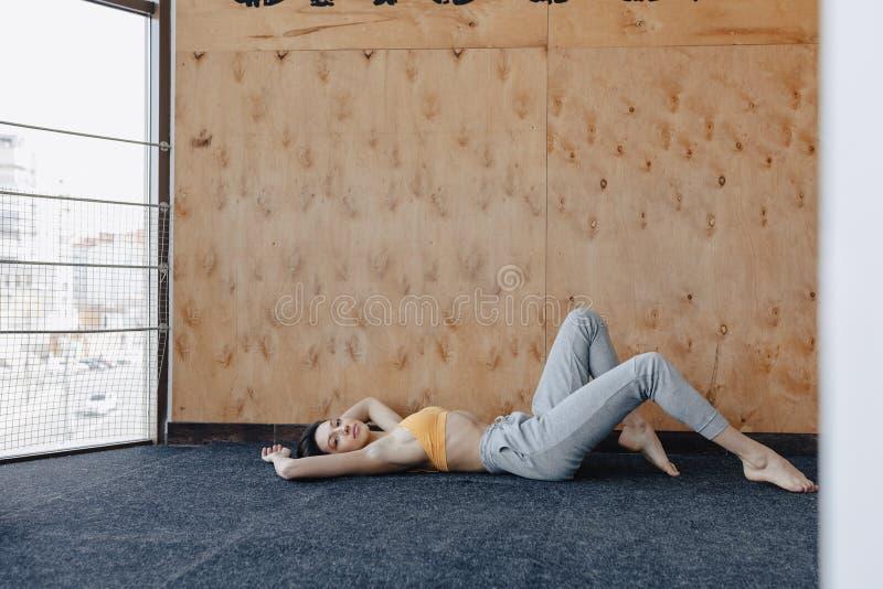 Giovane ragazza attraente che fa gli esercizi di forma fisica con yoga sul pavimento su un fondo di legno fotografia stock