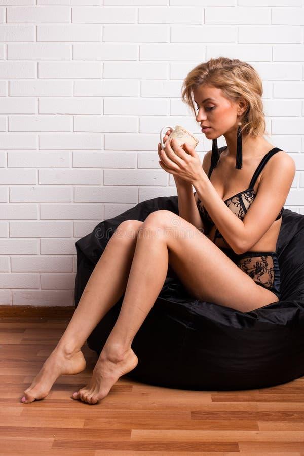 Giovane ragazza attraente che si siede su una sedia con un cappuccio di tè fotografie stock libere da diritti