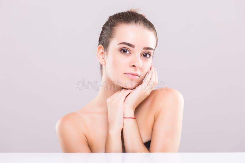 Giovane ragazza attraente con capelli neri riparati dietro, i grandi occhi, le sopracciglia spesse e le spalle nude tenenti mano  fotografia stock libera da diritti