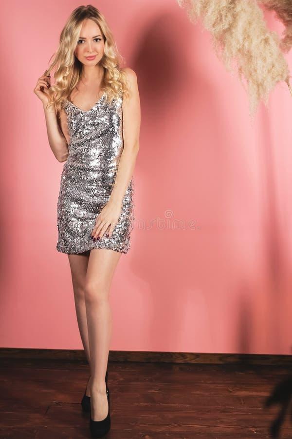 Giovane ragazza attraente del blondie che posa in un vestito d'argento brillante in uno studio della foto su un fondo rosa immagine stock libera da diritti