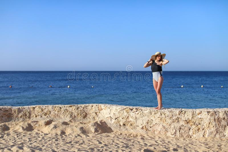 Giovane ragazza attraente sexy calda graziosa che si rilassa in costume da bagno sulle pietre con il mare blu e cielo su fondo Co immagine stock