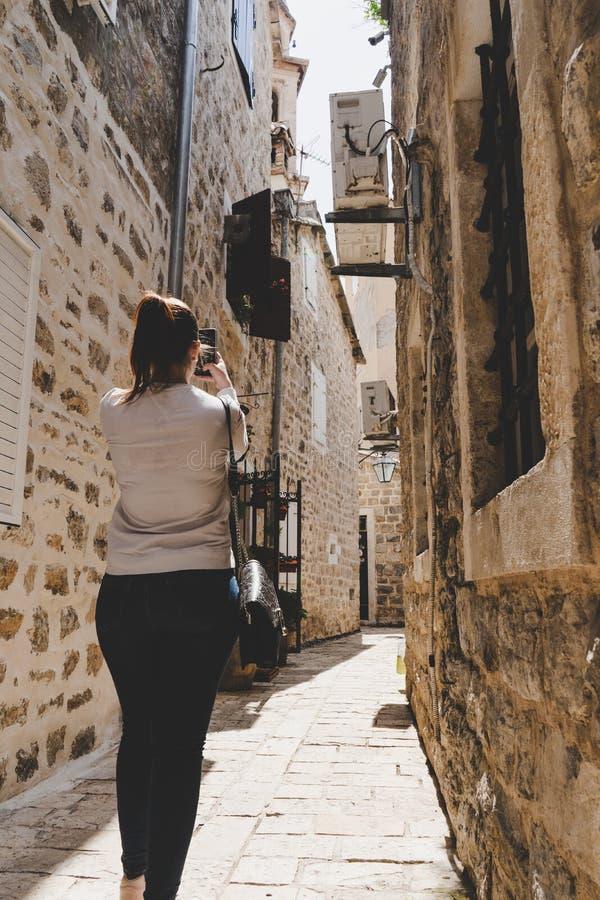 Giovane ragazza bianca che prende le immagini nelle piccole vie strette di vecchia città di Budua, Montenegro Donna che cammina f immagine stock