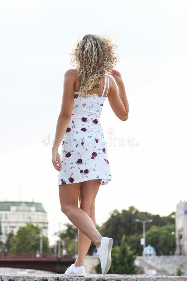 Giovane ragazza bionda attraente che cammina sulla parete fotografia stock libera da diritti