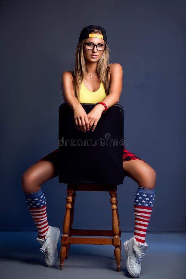 Giovane ragazza bionda attraente che si siede sulla sedia immagini stock libere da diritti