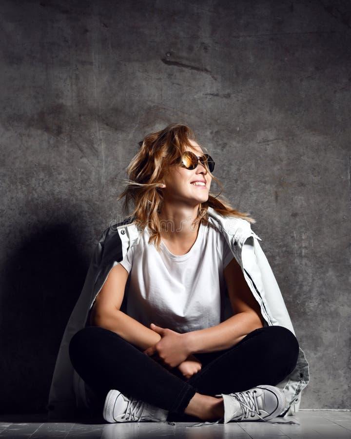Giovane ragazza bionda che si siede su un pavimento e che esamina macchina fotografica fotografia stock