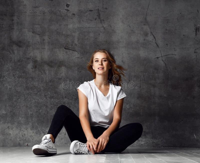 Giovane ragazza bionda che si siede su un pavimento e che esamina macchina fotografica immagini stock