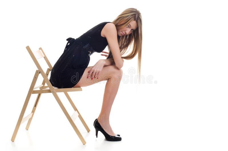 Giovane ragazza bionda che si siede su una presidenza immagine stock libera da diritti