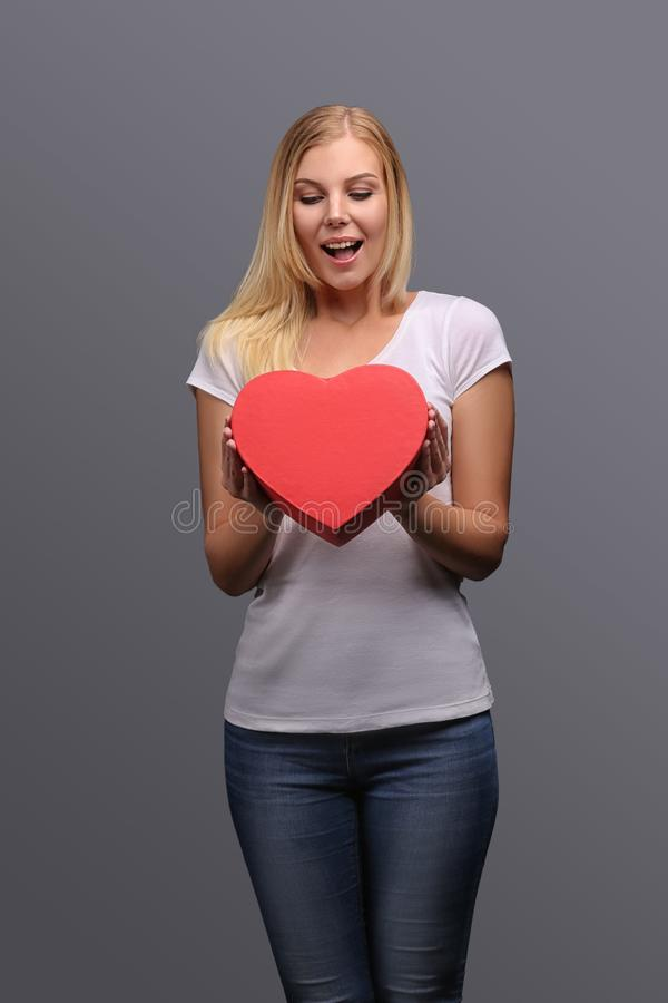Giovane ragazza bionda con il regalo a disposizione, rosso sotto forma di un cuore Emozioni di gioia e della sorpresa sul fronte  immagini stock libere da diritti