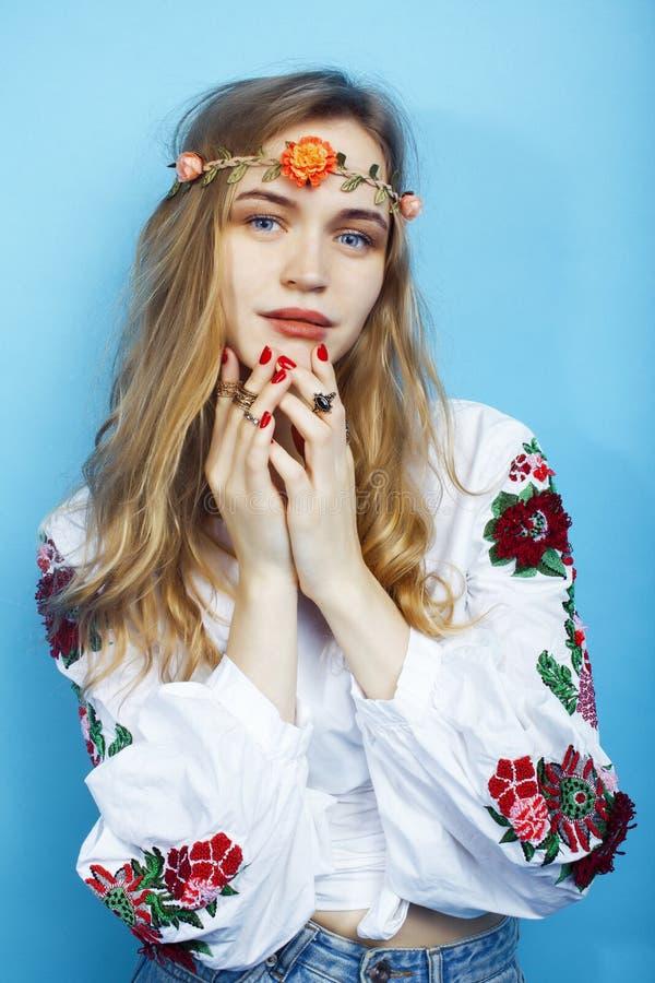 Giovane ragazza bionda graziosa che posa sul fondo blu, fiori di boho di hippy di stile di modo sulla testa fotografie stock libere da diritti