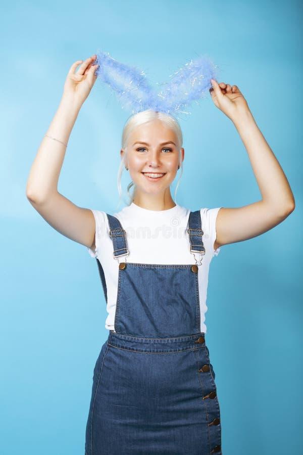 Giovane ragazza bionda graziosa con la posa delle orecchie di coniglio allegra sul blu immagini stock libere da diritti