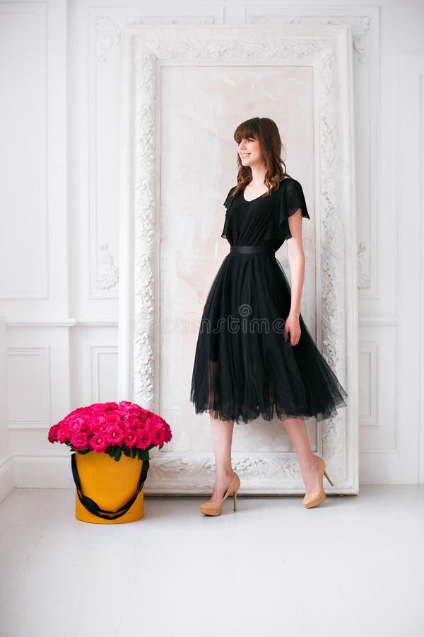 Giovane ragazza bionda piacevole in vestito nero e scarpe sui tacchi alti odorare fiorisce tenendo il mazzo porpora delle rose in immagine stock libera da diritti