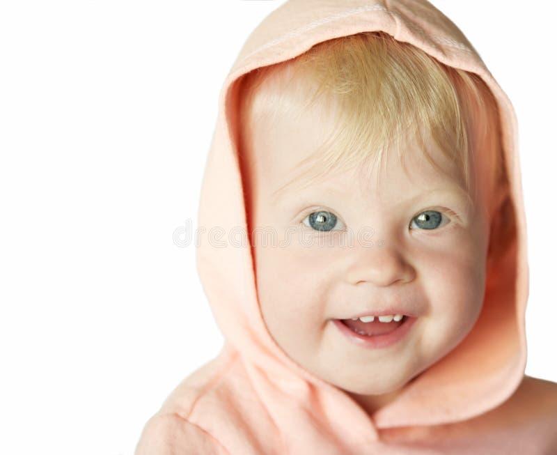 Giovane ragazza bionda sorridente in cappuccio rosa nel bianco