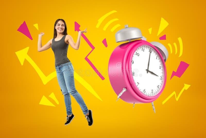 Giovane ragazza castana felice che porta i jeans e maglietta casuali con le frecce rosa del fumetto e della sveglia su fondo gial illustrazione vettoriale