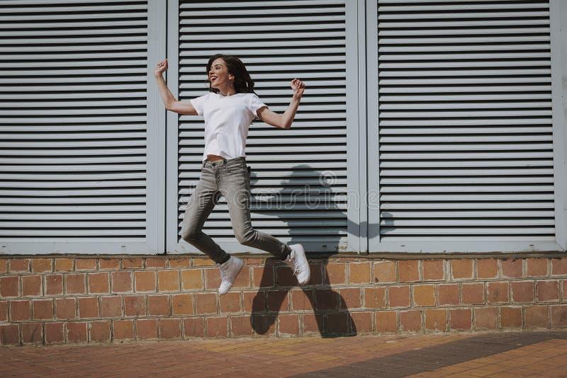Giovane ragazza castana felice dei pantaloni a vita bassa che salta su fotografia stock