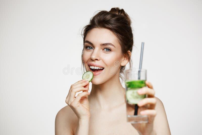 Giovane ragazza castana positiva che sorride esaminando macchina fotografica che mangia la fetta del cetriolo che tiene bicchiere fotografia stock libera da diritti