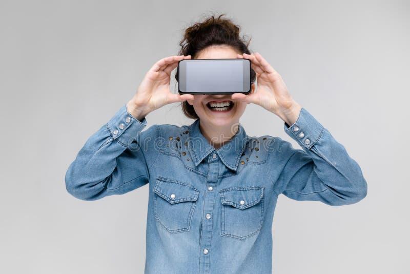 Giovane ragazza castana in vetri rotondi I capelli sono riuniti in un panino Ragazza con un telefono nero La ragazza ha coperto i fotografia stock libera da diritti