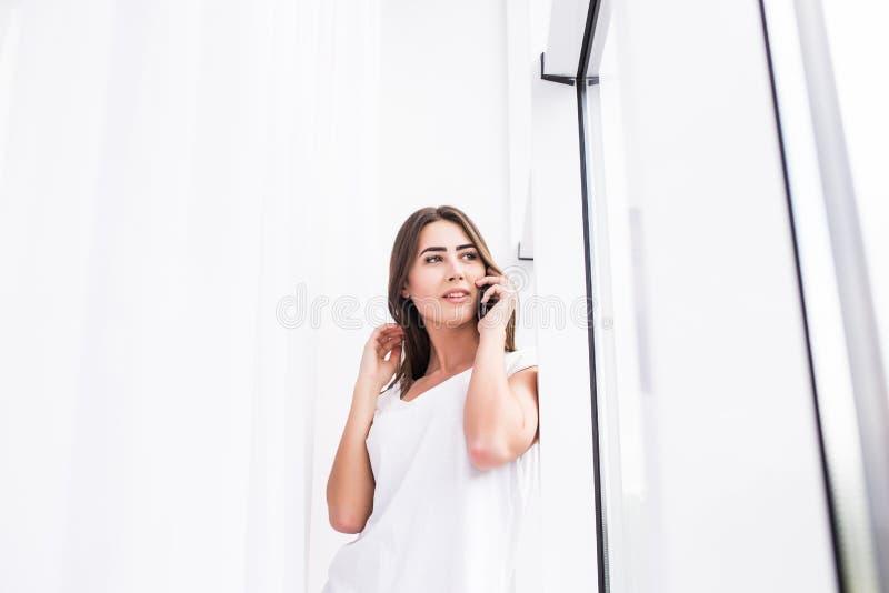 Giovane ragazza caucasica sorridente attraente che sta sul fondo della finestra, parlante per telefono cellulare immagini stock