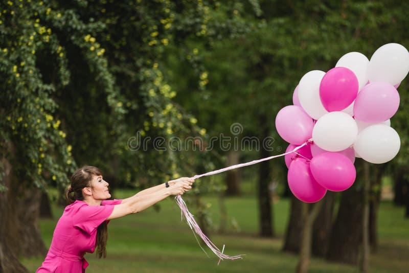 Giovane ragazza caucasica weared nei giochi rosa del vestito con i palloni rosa immagine stock libera da diritti