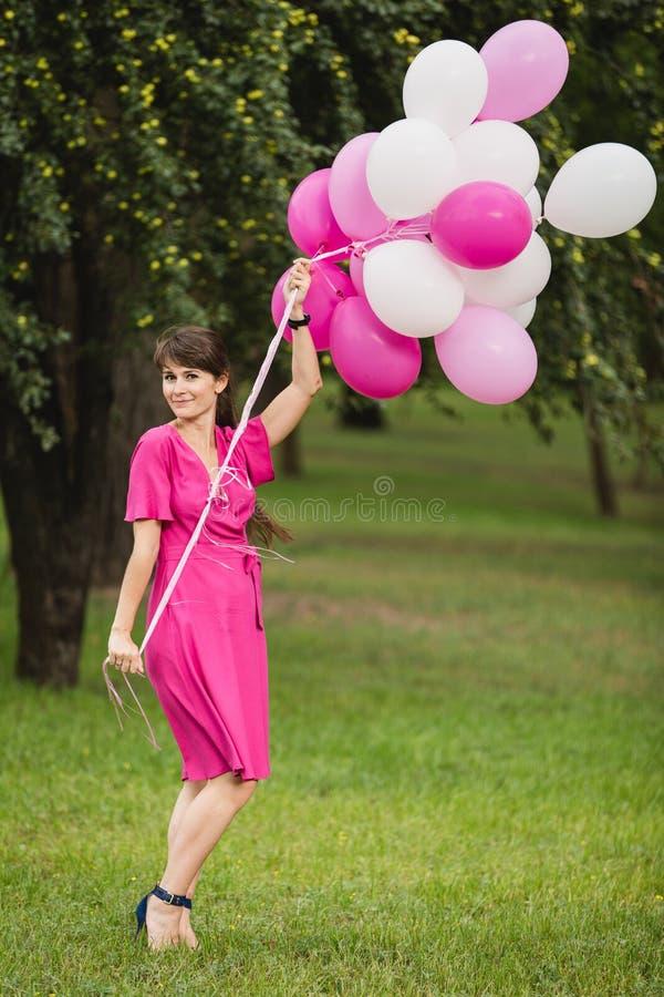Giovane ragazza caucasica weared nei giochi rosa del vestito con i palloni rosa fotografie stock libere da diritti