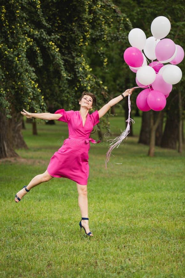 Giovane ragazza caucasica weared nei giochi rosa del vestito con i palloni rosa fotografia stock
