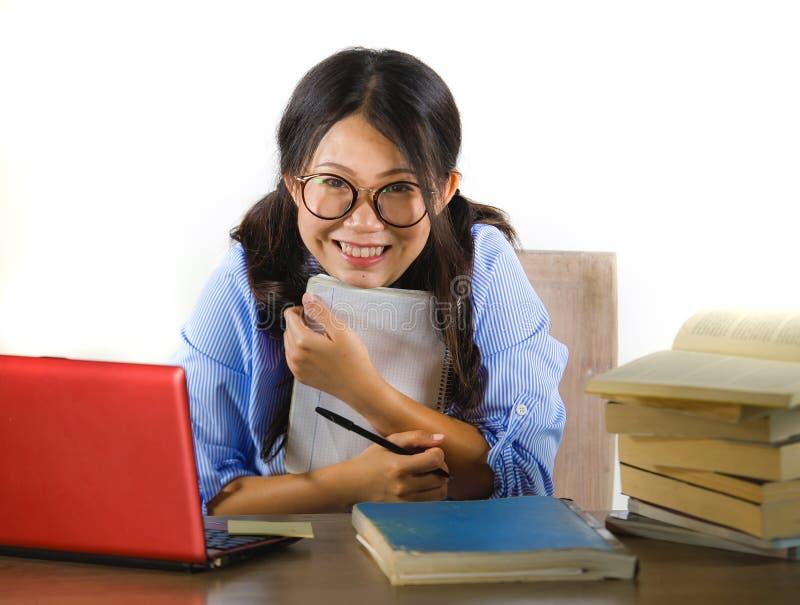 Giovane ragazza cinese asiatica dolce e felice dello studente nel funzionamento di vetro del nerd allegro sul computer portatile  fotografie stock libere da diritti