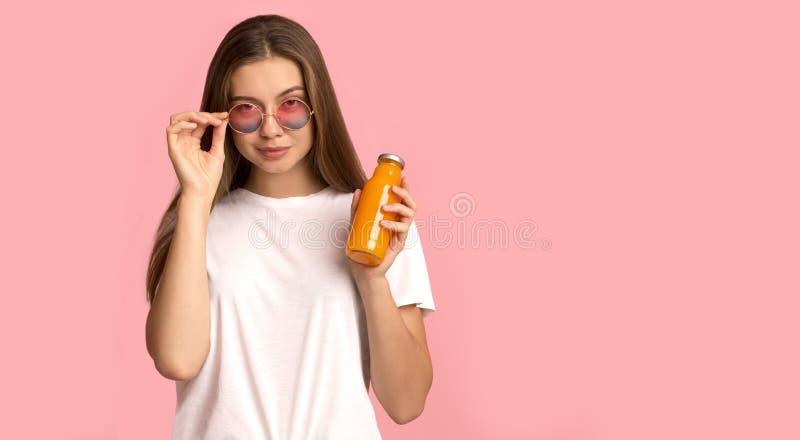Giovane ragazza con occhiali da sole che porta un bicchiere di detox arancione in vaso di vetro immagine stock