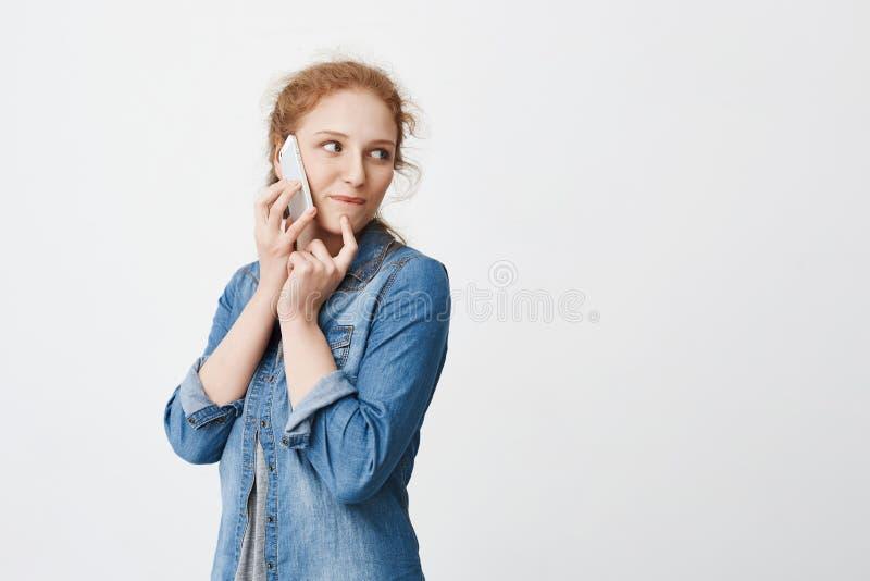 Giovane ragazza curiosa della testarossa che parla sullo smartphone mentre girando e guardando giusto, tenendo mano vicino al lab immagini stock