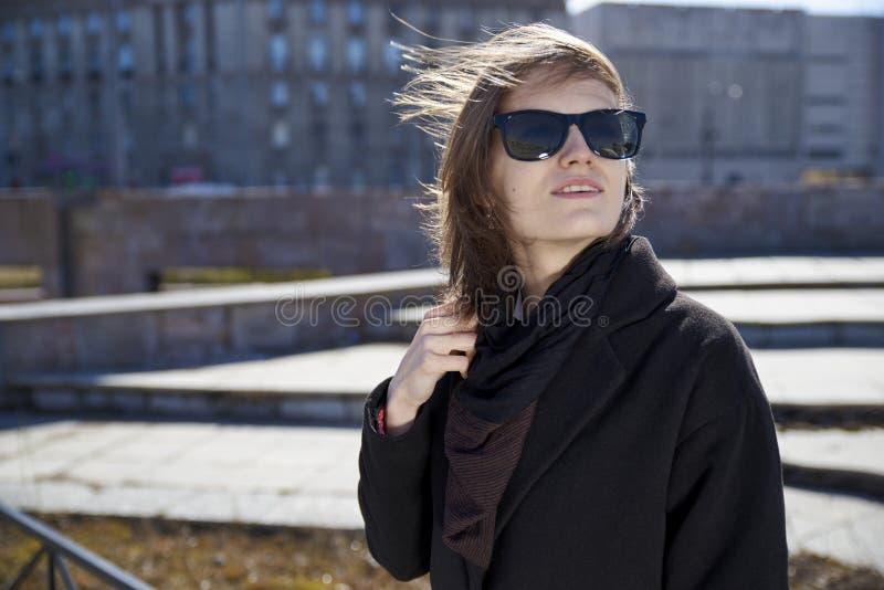 Giovane ragazza dai capelli corti in occhiali da sole e cappotto nero alla moda che posano per il ritratto sul fondo urbano grigi immagine stock