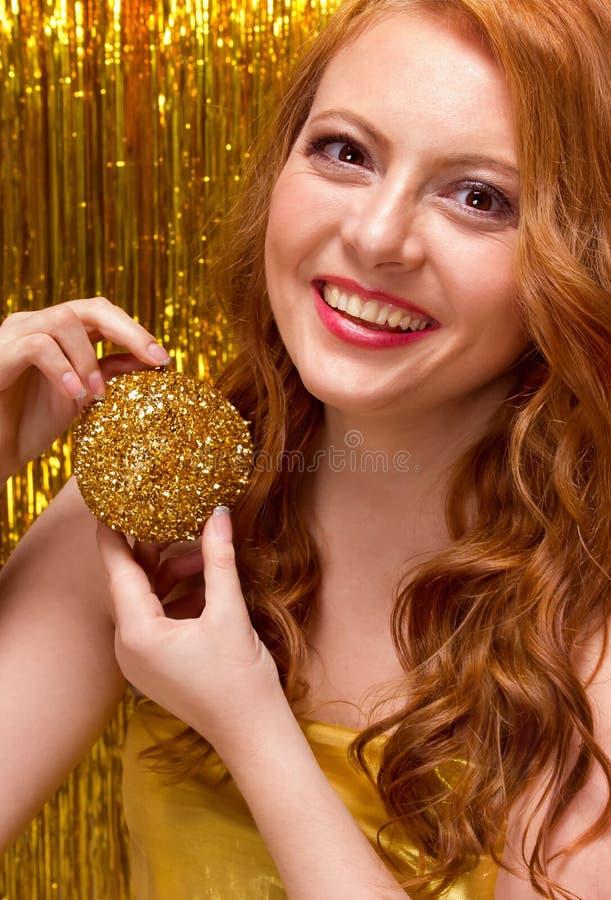 Giovane ragazza dai capelli rossi su un fondo dell'oro fotografia stock libera da diritti