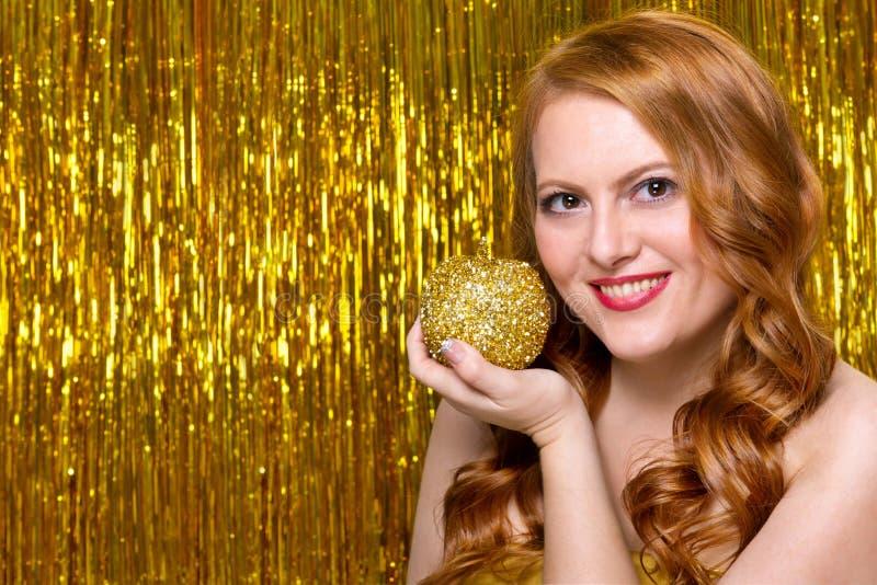Giovane ragazza dai capelli rossi su un fondo dell'oro fotografia stock