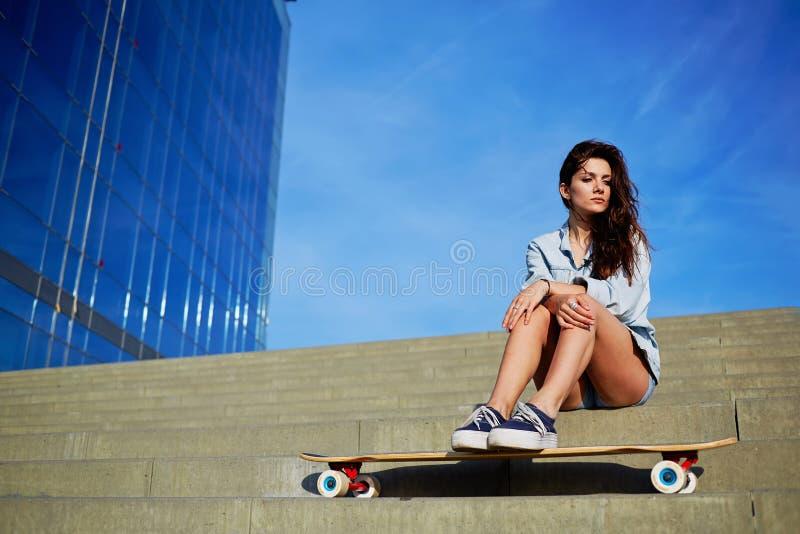 Giovane ragazza dei pantaloni a vita bassa che posa a distogliere lo sguardo leggero di bello tramonto immagini stock