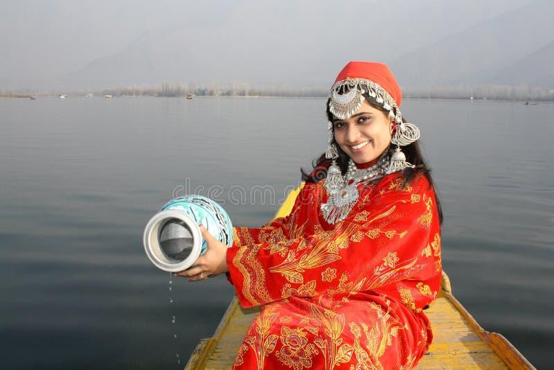 Giovane ragazza del Kashmir che raccoglie acqua dal lago dal immagine stock libera da diritti