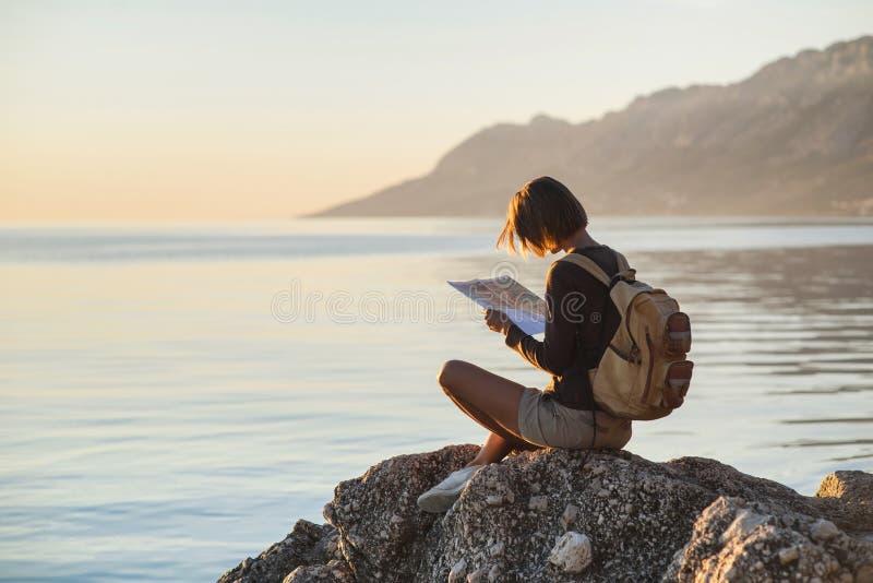 Giovane ragazza del viaggiatore che si siede con la mappa vicino al mare al tramonto, al viaggio, all'escursione ed al concetto a immagine stock