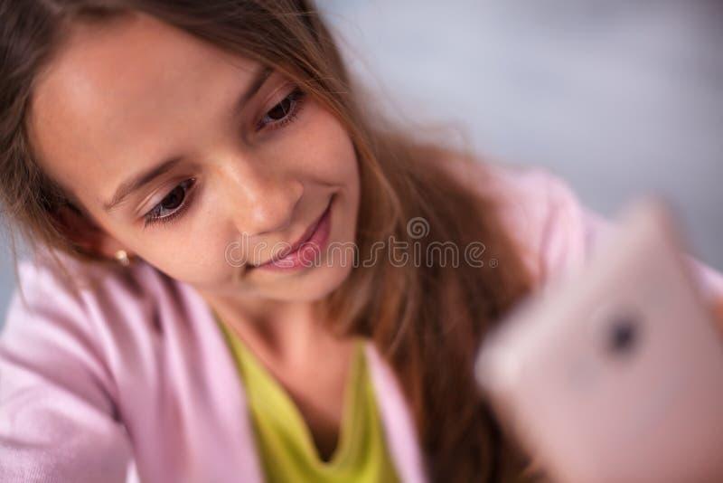 Giovane ragazza dell'adolescente che prende un selfie sveglio con il suo telefono fotografia stock libera da diritti