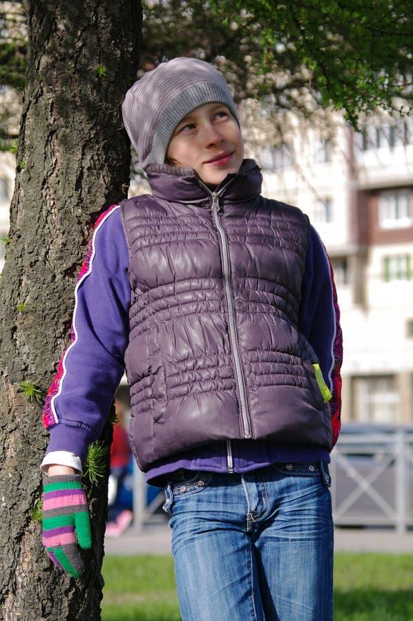 Giovane ragazza dell'adolescente che sta fra il tronco due in un parco immagine stock