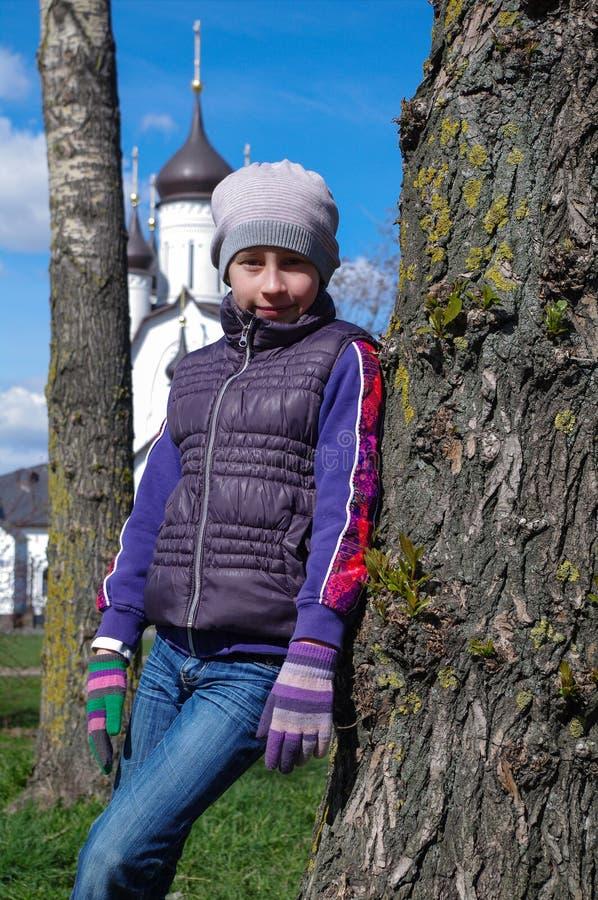 Giovane ragazza dell'adolescente che sta fra il tronco due in un parco con la chiesa nel fondo fotografie stock libere da diritti