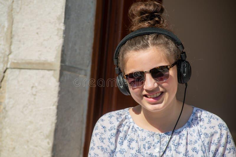 Giovane ragazza dell'adolescente con musica d'ascolto degli occhiali da sole all'aperto fotografia stock libera da diritti