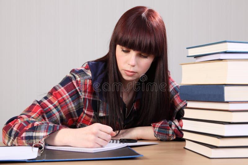 Giovane ragazza dell'allievo che fa scrittura di lavoro in libro fotografia stock