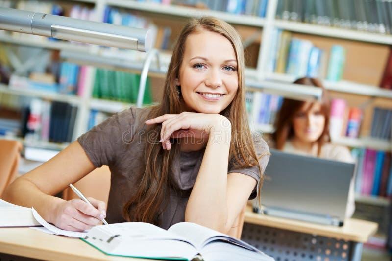 Giovane ragazza dell'allievo che lavora con il libro alla libreria immagine stock libera da diritti