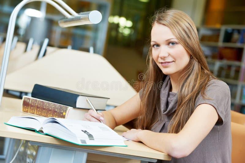 Giovane ragazza dell'allievo che lavora con il libro alla libreria fotografie stock libere da diritti