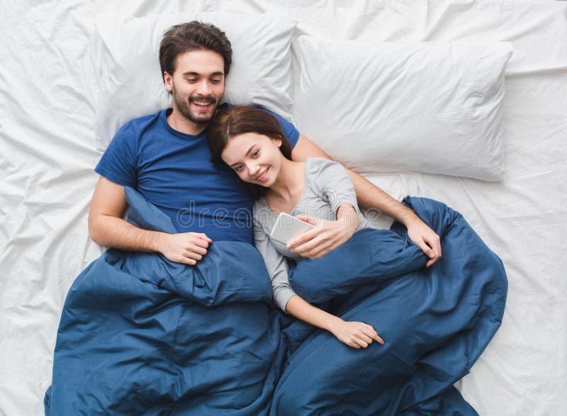 Giovane ragazza di concetto di mattina di punto di vista superiore delle coppie a letto che prende le foto del selfie fotografia stock libera da diritti